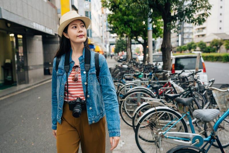 Giovane viaggio dell'uomo della lente che cammina sulla strada a Osaka Giappone molto parco della bicicletta dal lato della via a fotografia stock