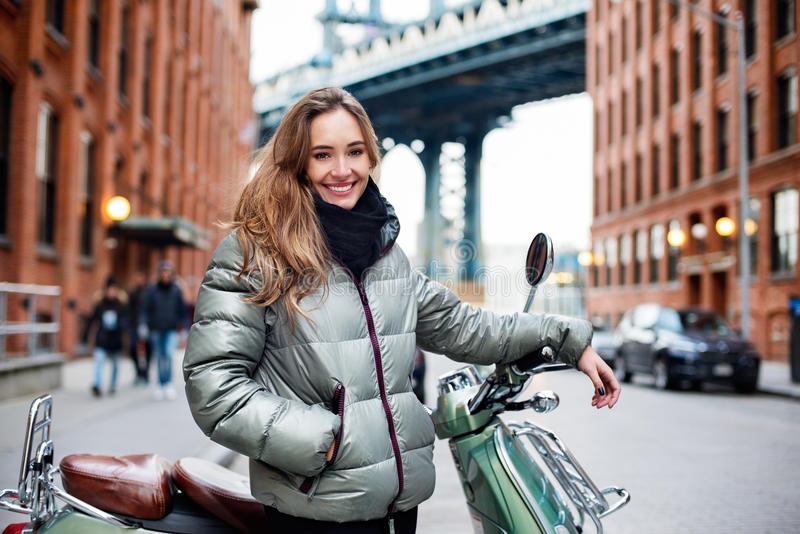 Giovane viaggio felice felice della donna sul motorino d'annata intorno a Brooklyn, New York fotografie stock libere da diritti