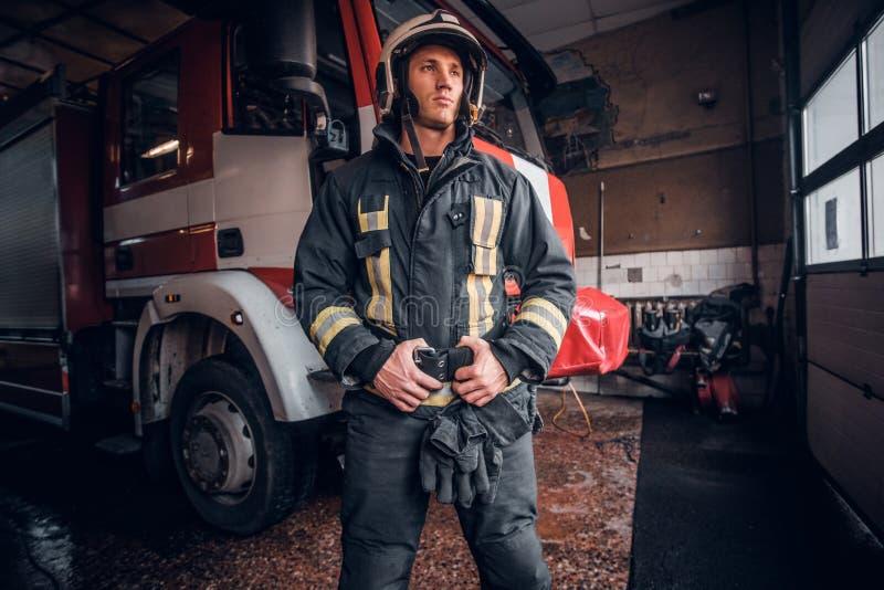 Giovane vigile del fuoco che indossa condizione uniforme protettiva accanto ad un'autopompa antincendio in un garage di un corpo  fotografia stock