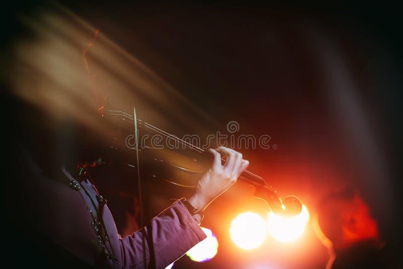 Giovane violinista Girl Performance con il suo strumento del violino sulla fase dell'interno di concerto Effetti della luce astra immagini stock