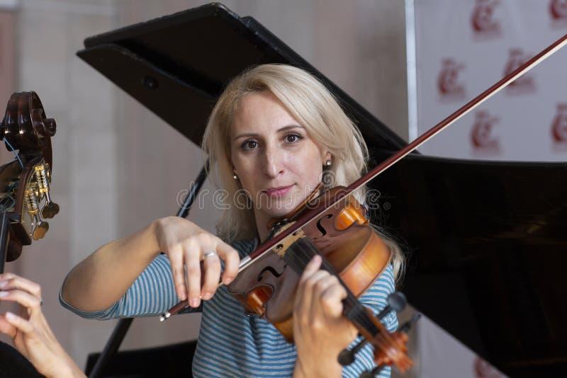 Giovane violino di gioco biondo positivo immagine stock