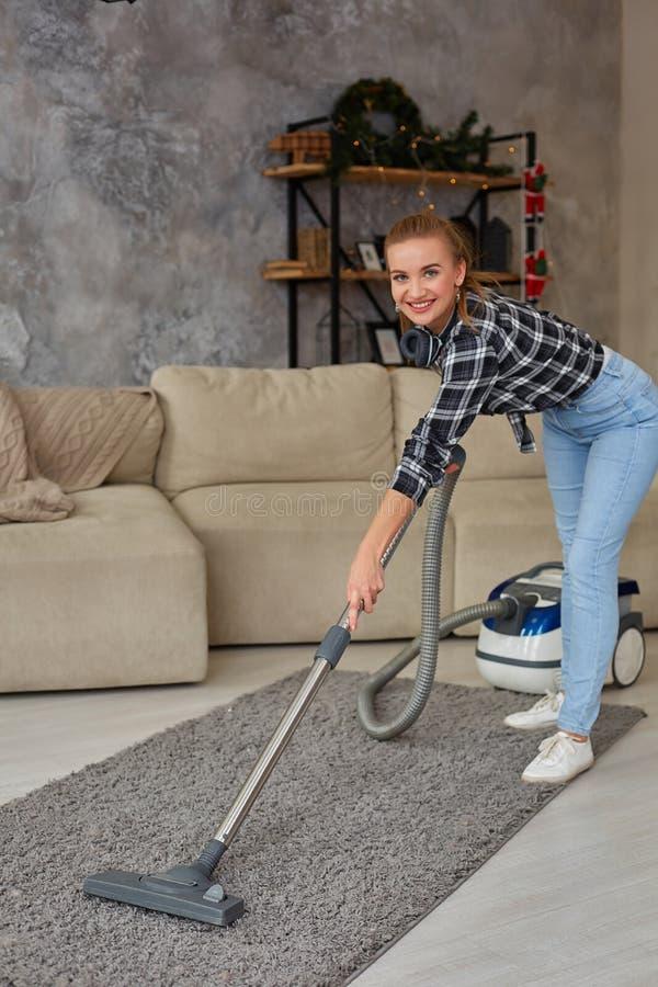 Giovane vuoto sorridente della donna che pulisce il tappeto nel salone, interno scandinavo moderno A casa, governo della casa immagine stock libera da diritti