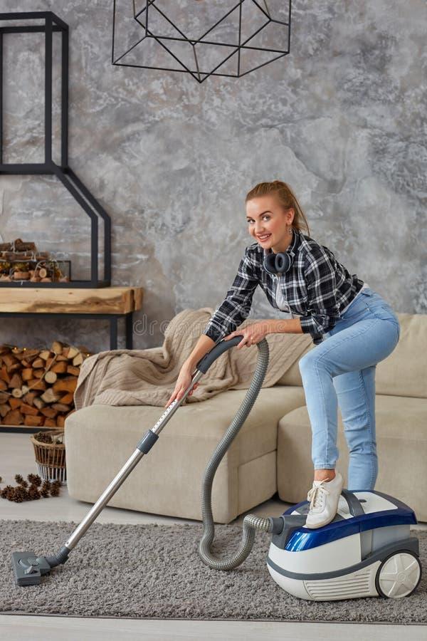 Giovane vuoto sorridente della donna che pulisce il tappeto nel salone, interno scandinavo moderno A casa, governo della casa fotografia stock