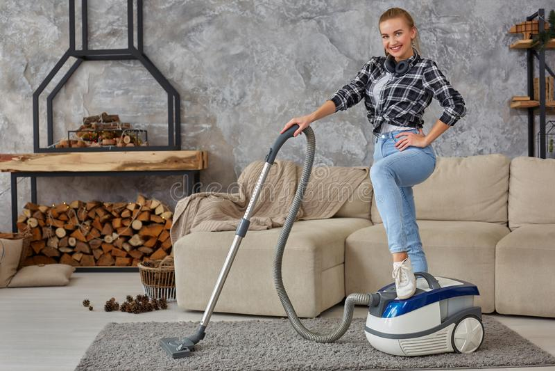 Giovane vuoto sorridente della donna che pulisce il tappeto nel salone, interno scandinavo moderno A casa, governo della casa fotografie stock