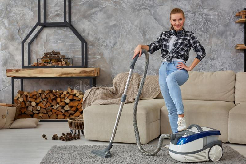 Giovane vuoto sorridente della donna che pulisce il tappeto nel salone, interno scandinavo moderno A casa, governo della casa immagini stock