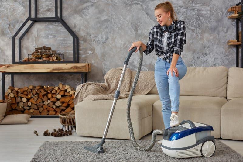 Giovane vuoto sorridente della donna che pulisce il tappeto nel salone, interno scandinavo moderno A casa, governo della casa fotografia stock libera da diritti