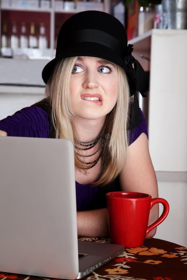 Giovane wamn preoccupato in caffè con il computer portatile immagini stock