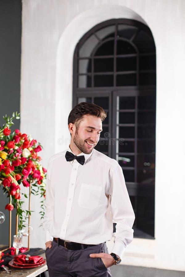 Giovane weared in classico vicino alla tavola decorata con i fiori rossi immagine stock libera da diritti