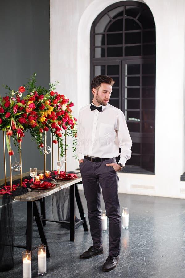 Giovane weared in classico vicino alla tavola decorata con i fiori rossi immagine stock
