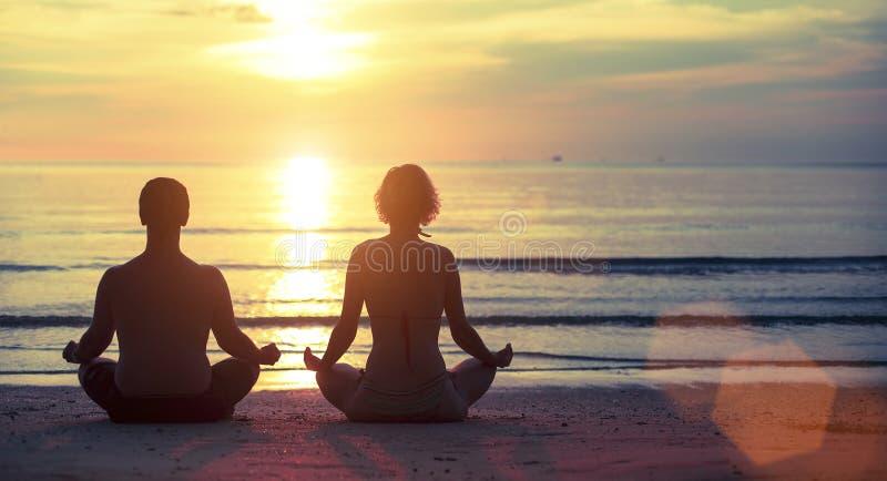 Giovane yoga delle coppie sulla spiaggia durante il tramonto distendasi fotografia stock libera da diritti