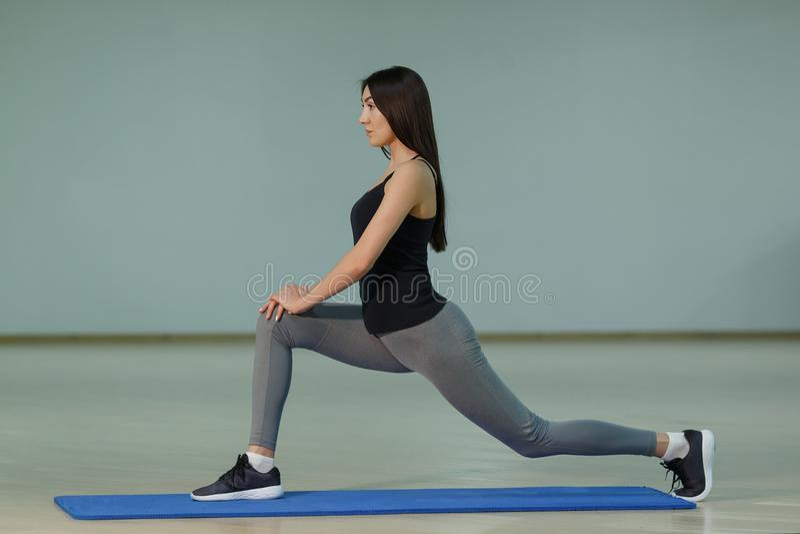 Giovane yoga di pratica sorridente attraente della donna sulla stuoia a casa fotografie stock libere da diritti