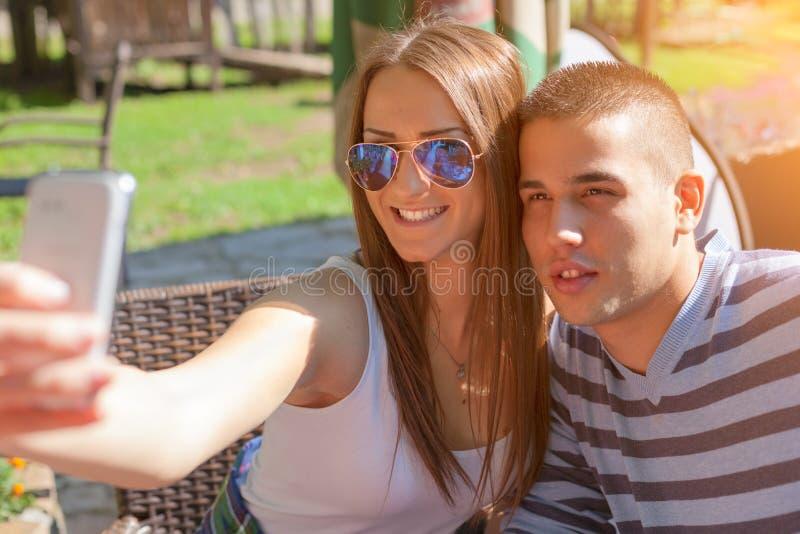 Giovani adolescenti delle coppie che sorridono e che prendono selfie all'aperto immagine stock