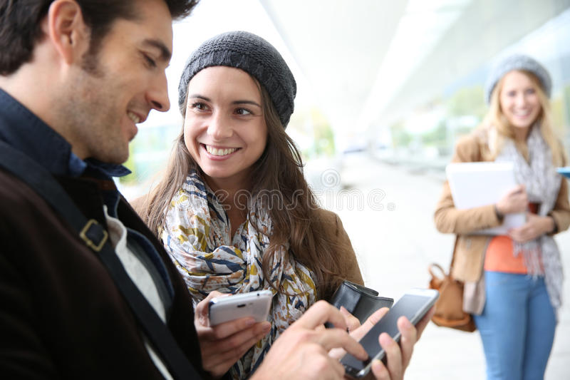 Giovani alla scuola facendo uso degli smartphones fotografie stock