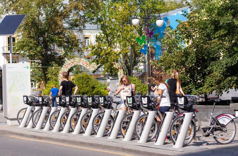 Giovani alla stazione locativa della bicicletta sulla via di Pyatnitskaya dentro immagine stock libera da diritti