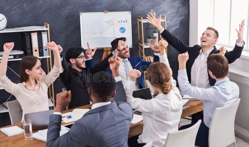 Giovani allegri che esaminano eccitati mentre sedendosi l'ufficio fotografia stock libera da diritti