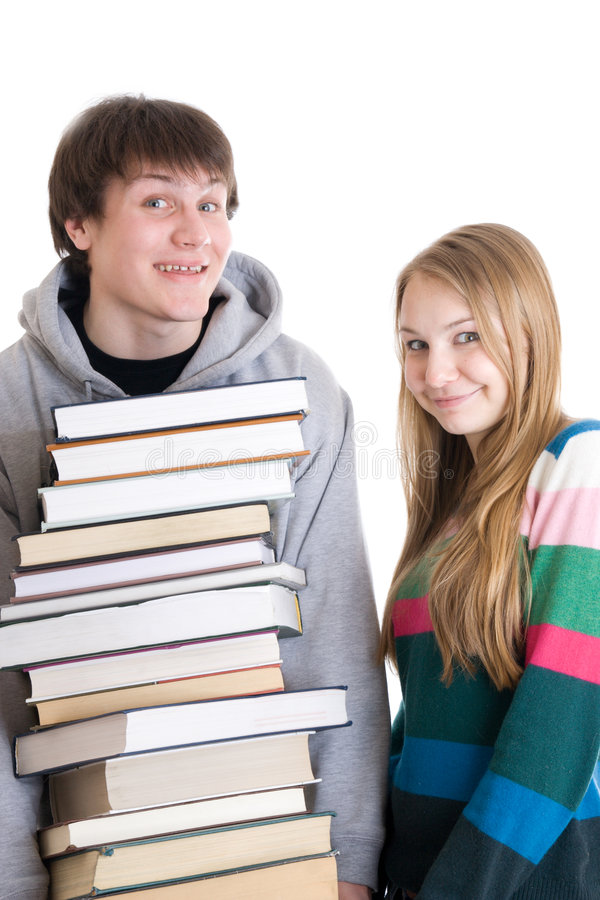 Giovani allievi di accoppiamenti con un mucchio dei libri isolati immagini stock