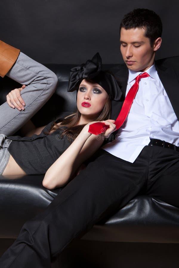 Giovani amanti sul sofà nero immagini stock libere da diritti