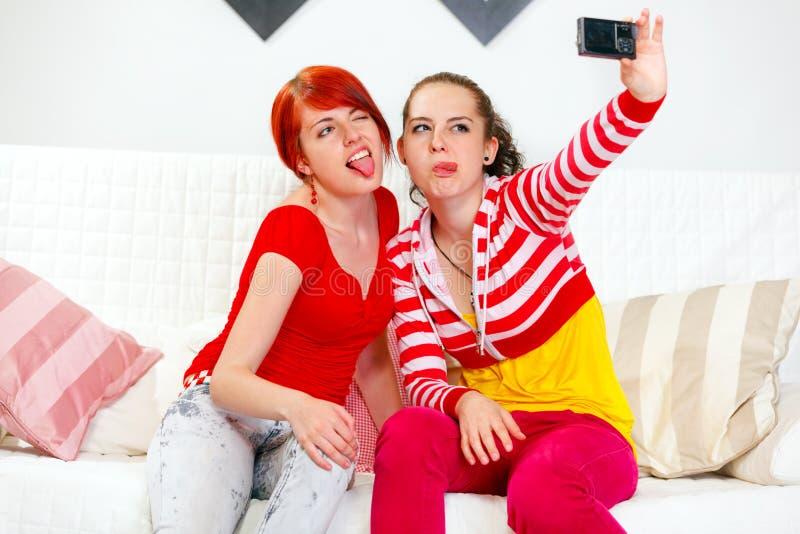Giovani amiche divertenti che si fotografano immagini stock
