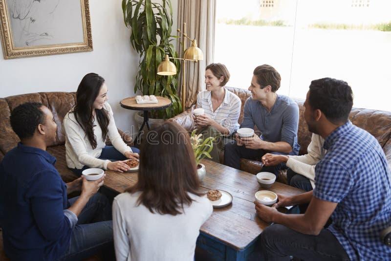 Giovani amici adulti che parlano intorno ad una tavola ad una caffetteria immagine stock