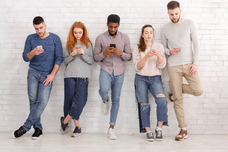 Giovani amici alla moda che per mezzo dei dispositivi sopra il muro di mattoni immagini stock