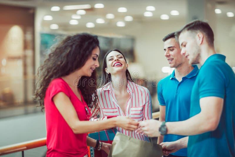 Giovani amici che comperano insieme nel centro commerciale fotografia stock
