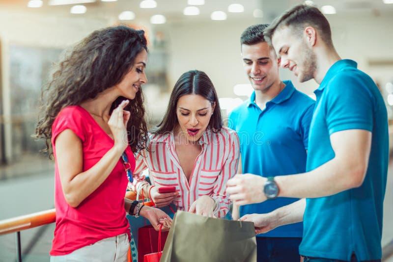 Giovani amici che comperano insieme nel centro commerciale immagine stock libera da diritti