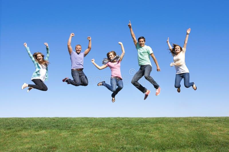 Giovani amici che saltano e che hanno divertimento fotografia stock libera da diritti