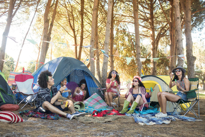 Giovani amici che si siedono insieme al campeggio fotografia stock libera da diritti