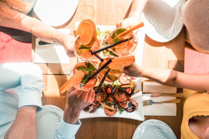 Giovani amici che tostano con i cocktail prima del cibo dei frutti di mare fotografie stock libere da diritti