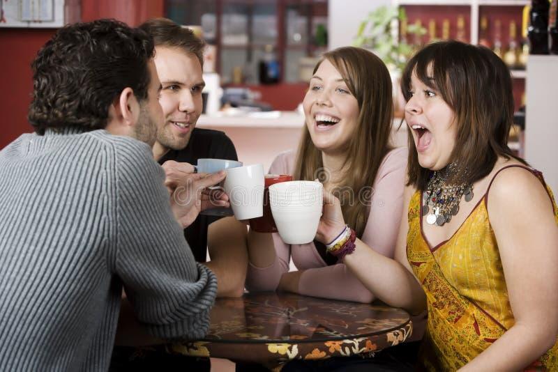 Giovani amici che tostano con le tazze di caffè immagini stock
