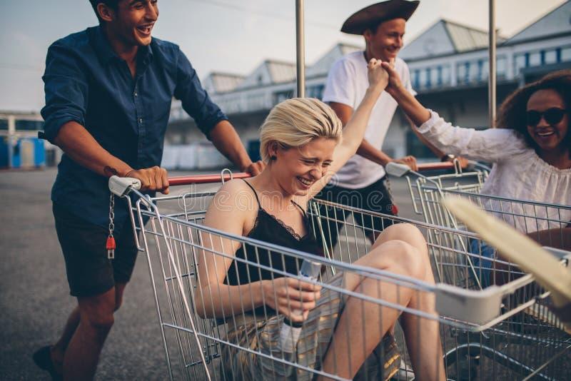 Giovani amici divertendosi sull'i carrelli fotografia stock libera da diritti
