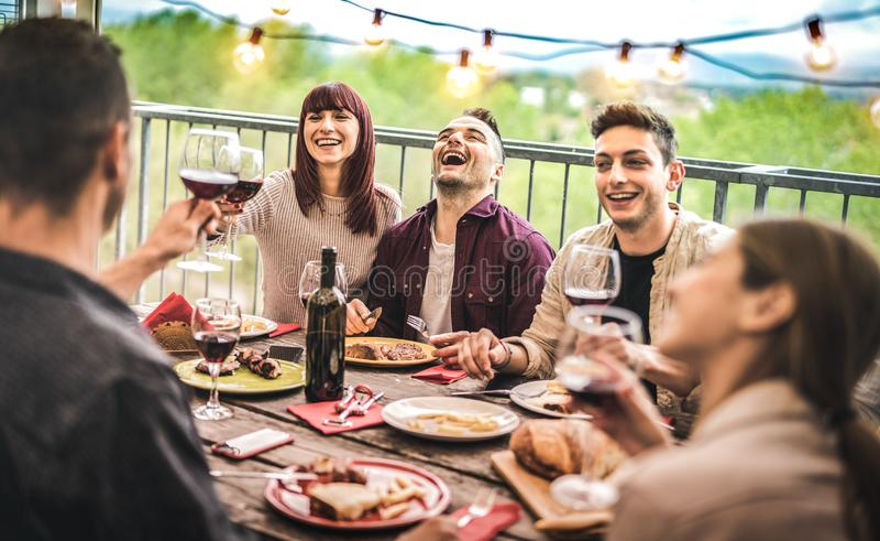 Giovani amici divertendosi vino rosso bevente al partito di cena dell'attico del balcone - gente felice che mangia l'alimento del fotografia stock