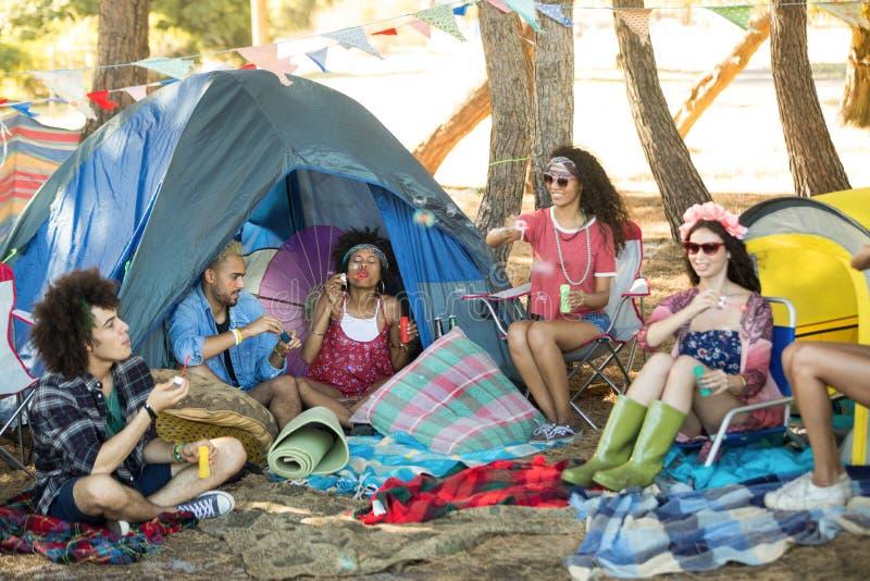 Giovani amici felici che godono al campeggio immagine stock libera da diritti
