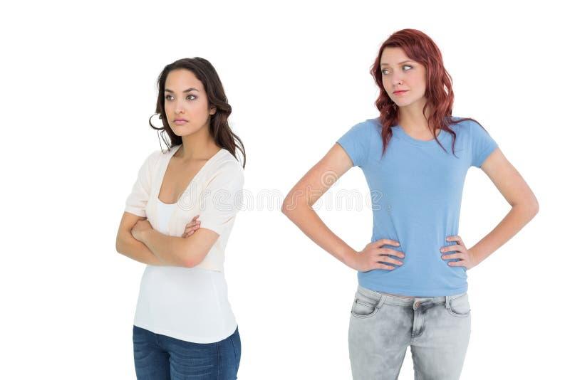 Giovani amici femminili infelici che non parlano dopo la discussione fotografia stock libera da diritti