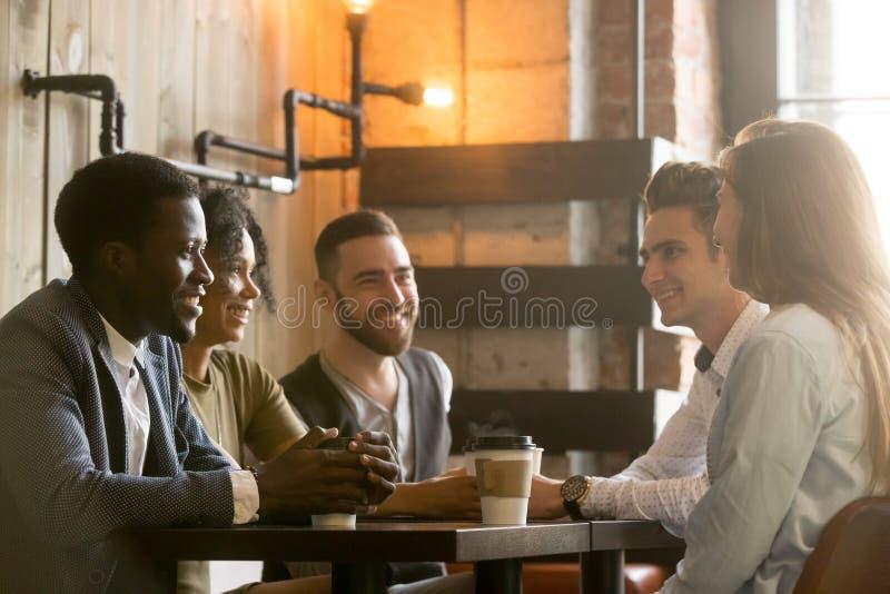 Giovani amici multirazziali che parlano e che bevono caffè che divide il co immagine stock