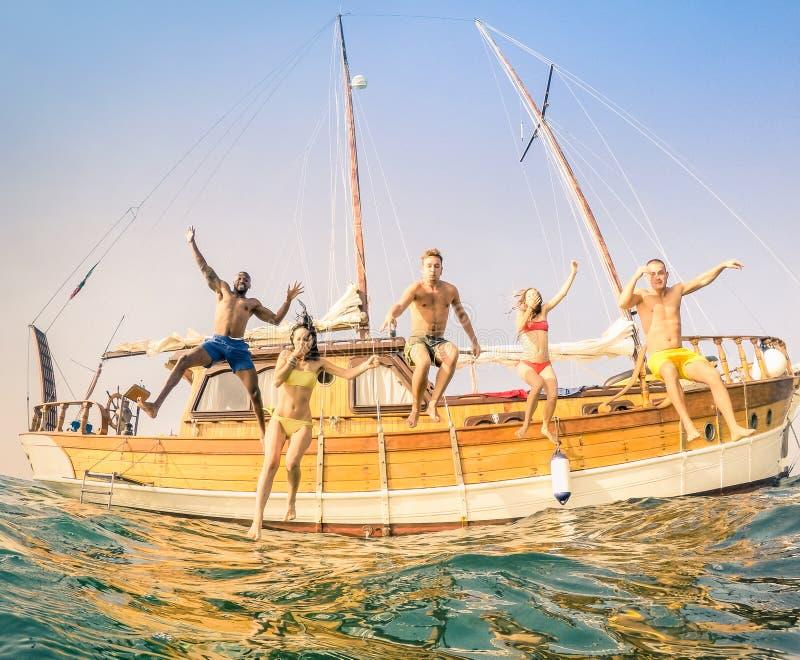 Giovani amici multirazziali che saltano dalla barca a vela di legno immagini stock