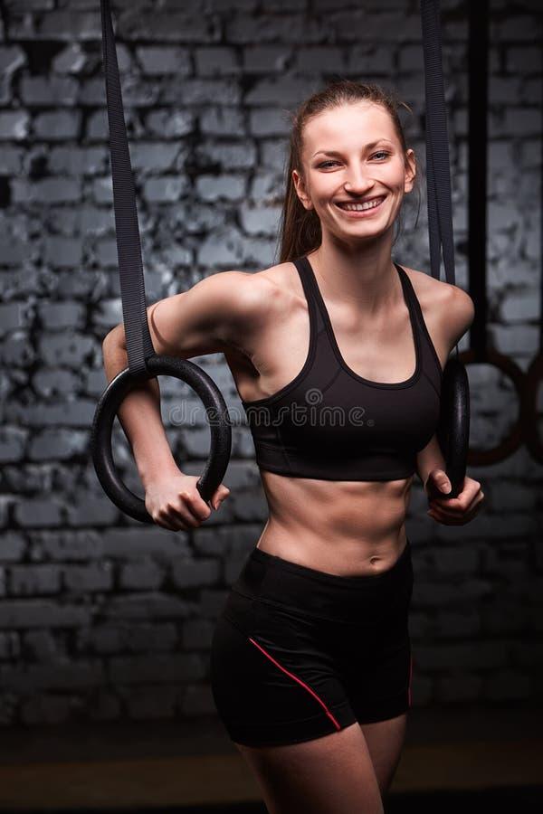 Giovani anelli sportivi adatti della ginnasta della tenuta della donna e sorridere alla palestra adatta dell'incrocio contro il m immagini stock libere da diritti