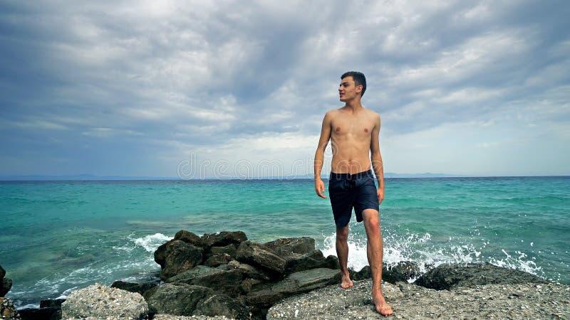 Giovani anni dell'adolescenza adatti felici che camminano sulle rocce che godono della vacanza immagine stock