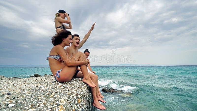 Giovani anni dell'adolescenza allegri che si siedono dall'oceano al pilastro il giorno di vacanza estiva e che si divertono rilas fotografie stock libere da diritti