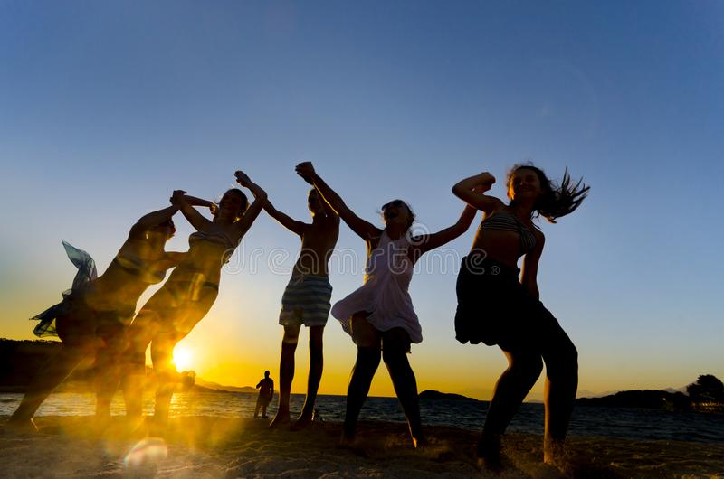 Giovani anni dell'adolescenza felici che ballano alla spiaggia al bello tramonto di estate fotografia stock libera da diritti