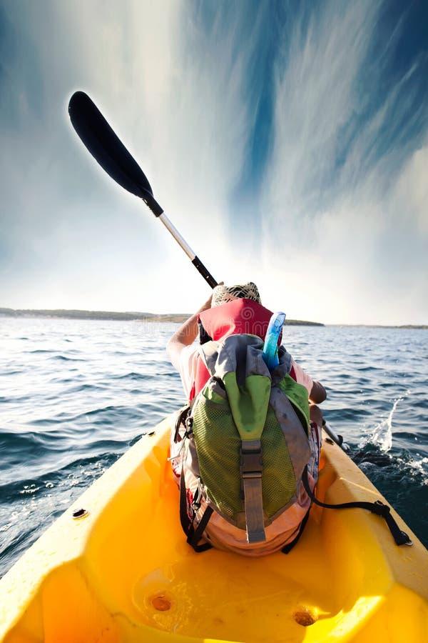 Giovani aratri del ragazzo attraverso le acque del mare con la sua canoa immagini stock libere da diritti