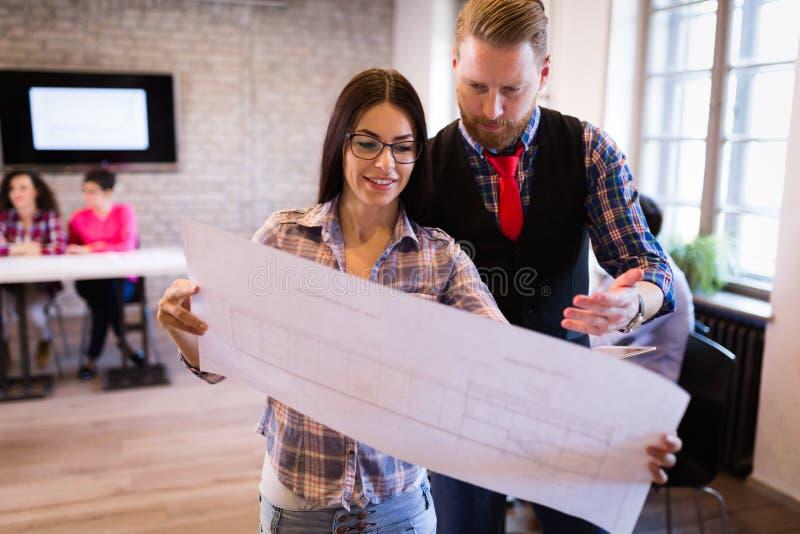 Giovani architetti attraenti che discutono nell'ufficio moderno immagini stock