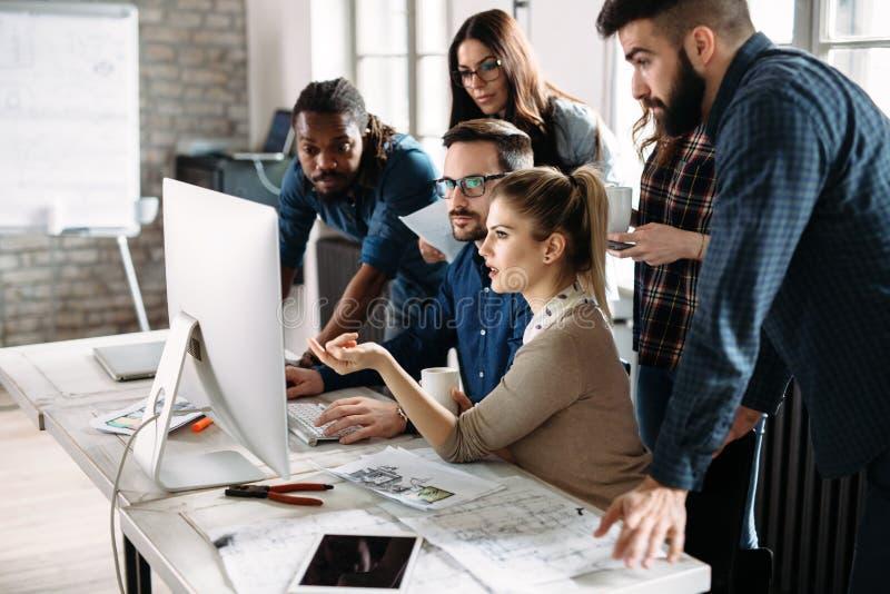 Giovani architetti che lavorano al progetto in ufficio immagini stock libere da diritti