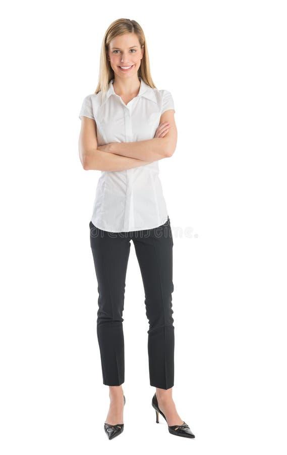 Giovani armi di Smiling While Standing della donna di affari attraversate fotografia stock libera da diritti