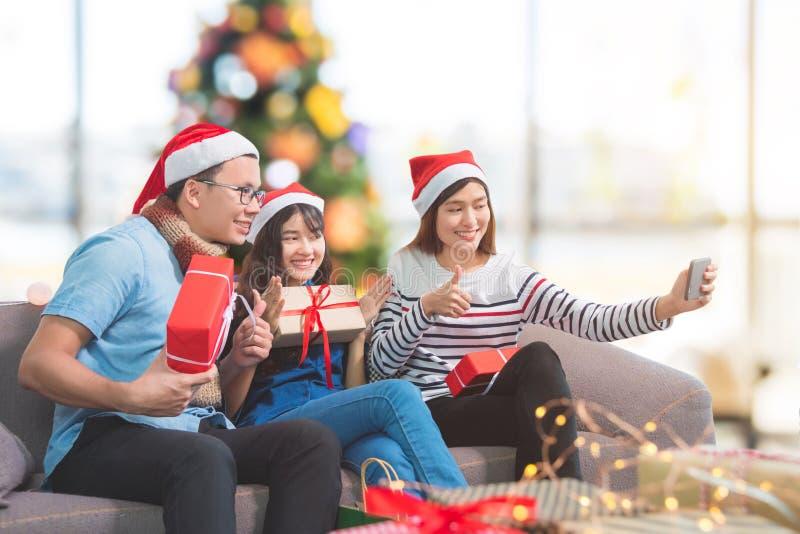 Giovani asiatici che prendono foto dal telefono cellulare nella festa di Natale immagini stock libere da diritti