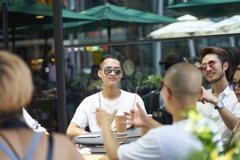 Giovani asiatici che si rilassano nella caffetteria fotografie stock