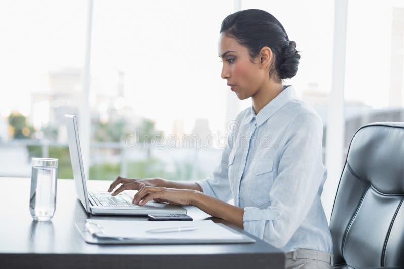 Giovani attentamente che lavorano donna di affari che si siede al suo scrittorio fotografia stock
