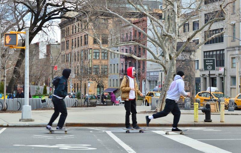 Giovani bambini dei pantaloni a vita bassa che guidano pattino nella città del Lower East Side di New York delle vie della città fotografia stock