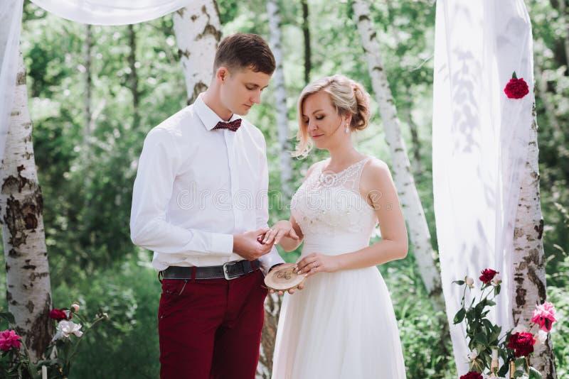 Giovani bei coppie, sposa e sposo nella foresta contro lo sfondo della decorazione di nozze immagini stock libere da diritti