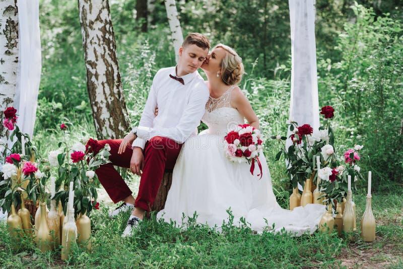 Giovani bei coppie, sposa e sposo nella foresta contro lo sfondo della decorazione di nozze immagine stock libera da diritti
